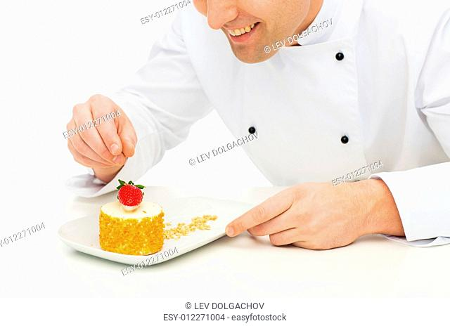 cooking, profession, haute cuisine, food and people concept - close up of happy male chef cook decorating dessert