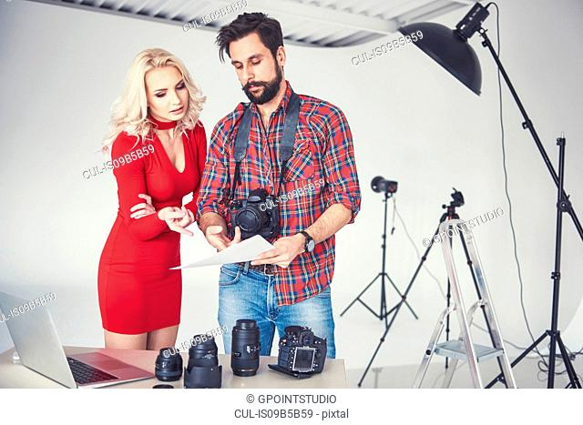 Male photographer and model looking at photographs from photo shoot in studio