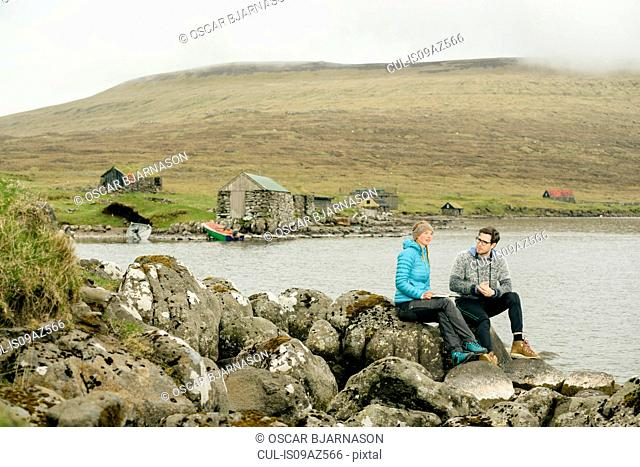 Couple relaxing on rocks by lake, Vagar, Faroe Islands