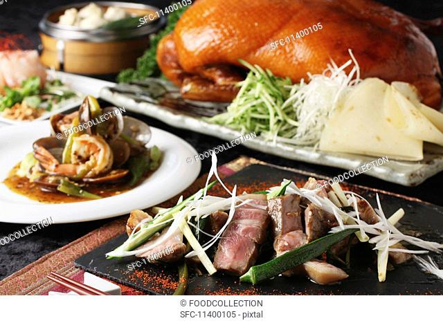 A Chinese buffet featuring grilled beef, Peking duck and prawns with vegetables