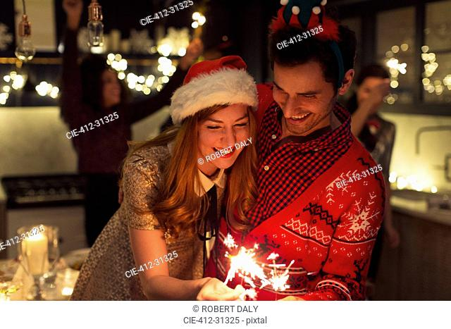 Playful couple with Christmas sparklers