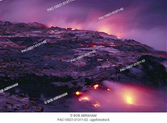 Hawaii, Big Island, Hawaii Volcanoes National Park, Lava flows into ocean at twilight, creating a purple mist