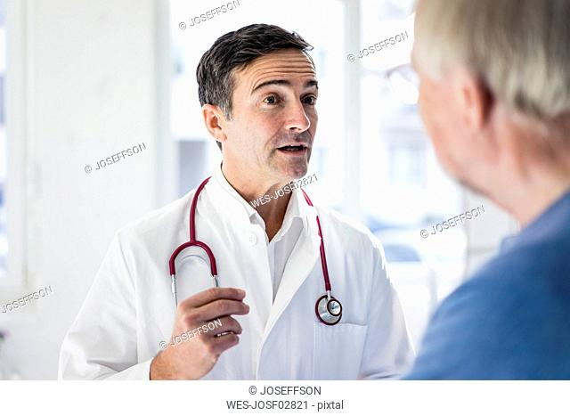 Portrait of doctor and talking to patient in medical practice