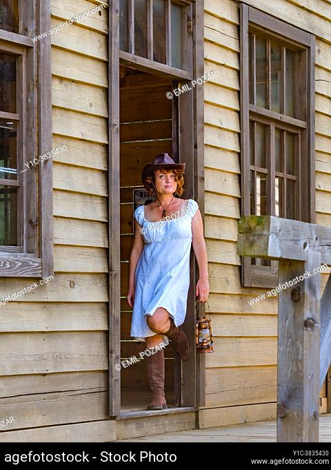 Mature woman in classic American West village environment on door frame