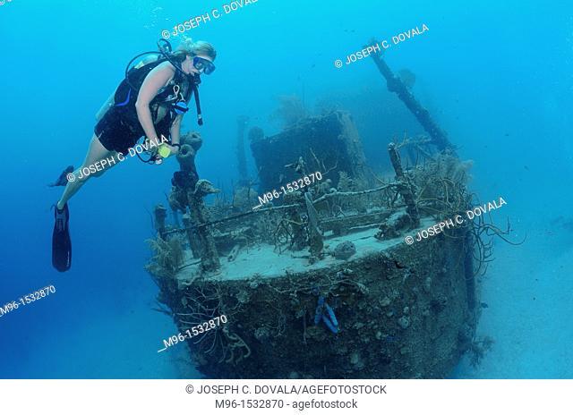 Scuba diver swims by sunken shipwreck, Roatan, Bay Islands, Honduras