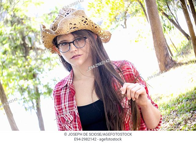 A casual portrait of a 26 year old woman with long brown hair and big glasses, on a country road
