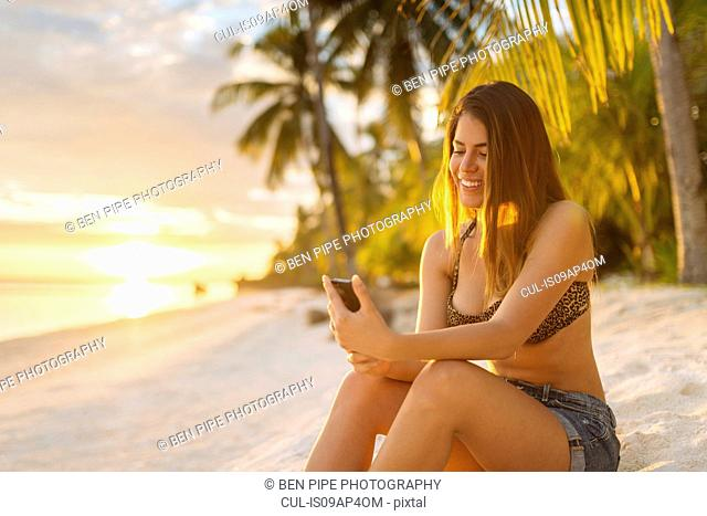 Young woman using smartphone on Anda beach, Bohol Province, Philippines