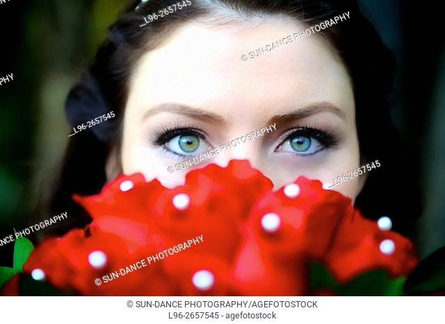 bride peeking over her red wedding bouquet - close up on beautiful eyes
