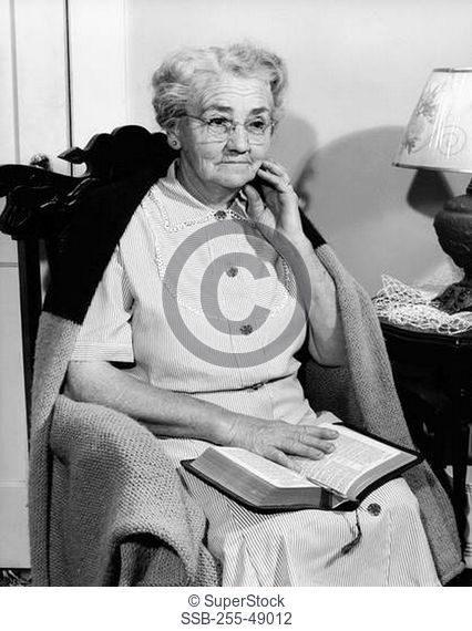 Senior woman sitting in a rocking chair with the Bible on her lap