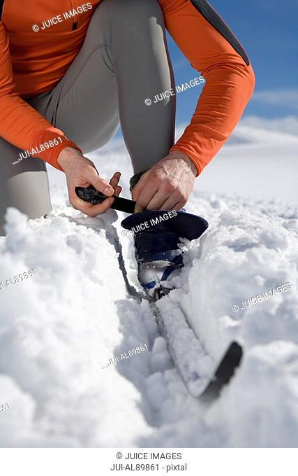 Man adjusting cross-country ski