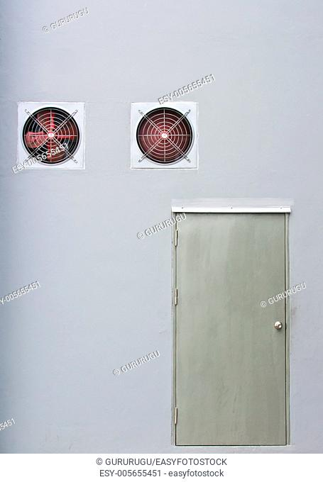 A pair of red industrial ventilated fan on grey wall with a stainless steel door as background