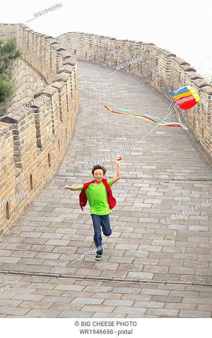 Boy running with a kite on the Great Wall of China, at Mutianyu, Huairou, China