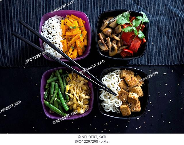 Four bowls with rice, roasted carrots, mushrooms, peppers, beans, mung beans, Mie noodles and tofu (Vegan)