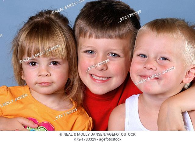 Three youngster posing, each showing different personality, miss independence, trying to please, and little stinker