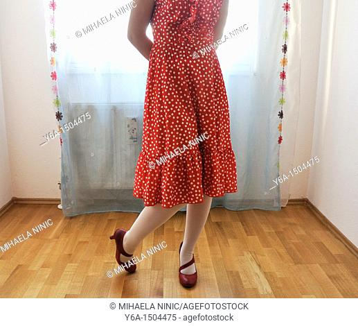 Young woman in red dress standing indoors