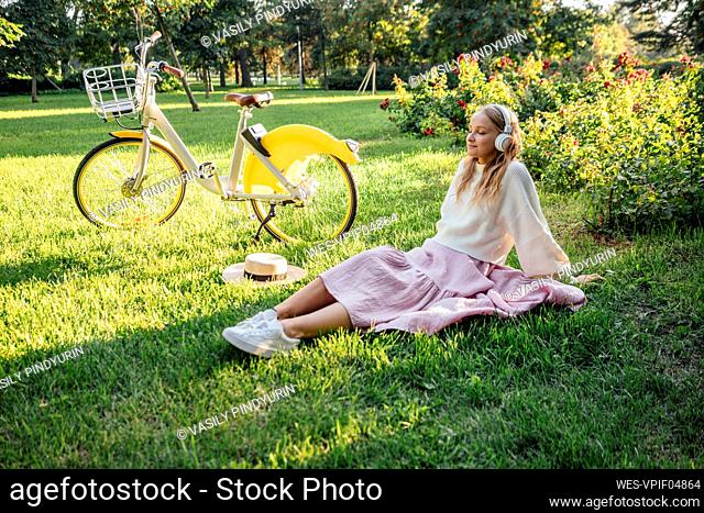 Young woman listening music through wireless headphones while sitting by bicycle at park