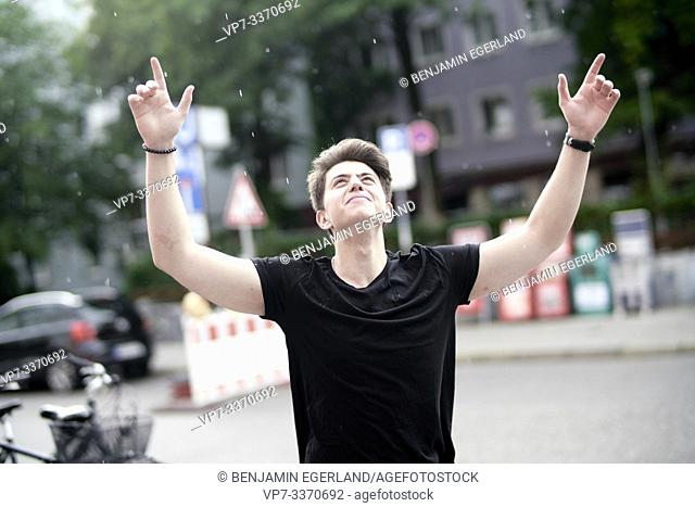 Happy young man celebrating on the street with arms raised