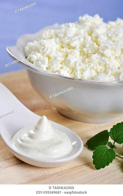Cottage cheese in bowl with sour cream on wooden cutting board