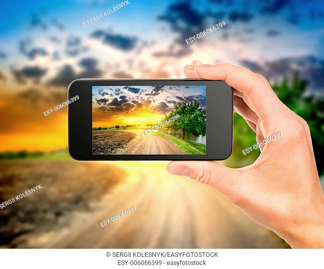 Mobile phone in hand and evening landscape