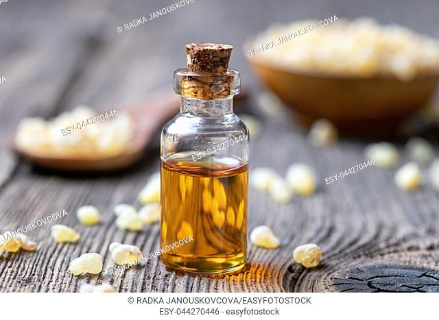 A bottle of essential oil with frankincense resin on a table