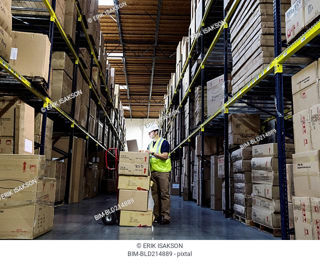 Caucasian worker using laptop in warehouse