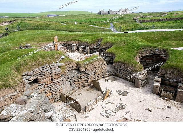 Europe, Scotland, Orkney - the Neolithic village of Skara Brae with Skaill House in the background