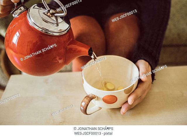 Woman pouring water into tea cup with chopped fresh ginger, close-up