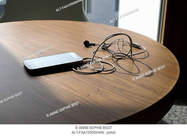 Smartphone and earbuds on table