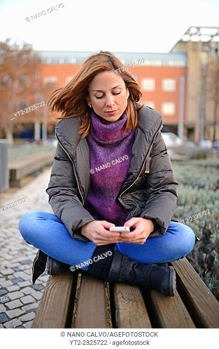 Attractive young woman using mobile phone outdoors