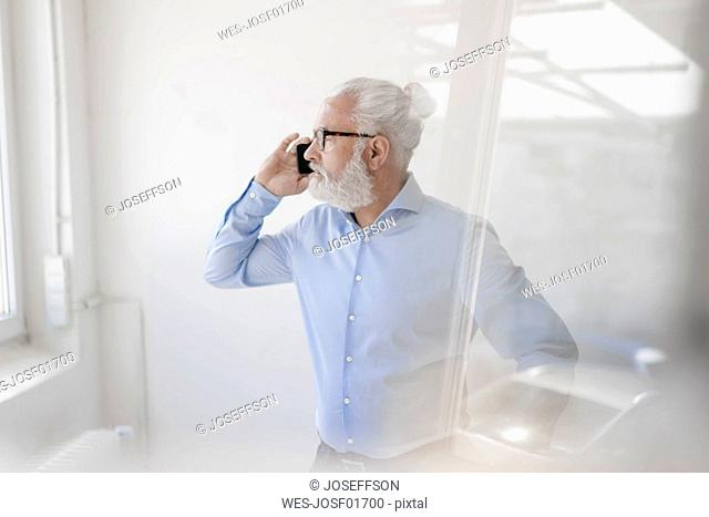 Mature man with beard and glasses on cell phone