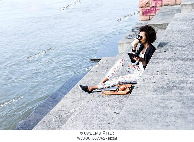 Young businesswoman with digital tablet drinking coffee to go at riverside