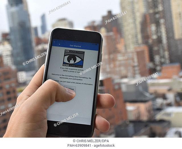 A user holds a smart phone in his hand which displays the terrorism alert app 'See something, say something' on the Upper East Side in New York, USA
