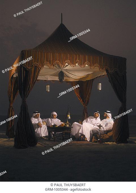 Ramadan: Arab men sitting in Arabian tent for Iftar (fast-breaking meal after sunset)