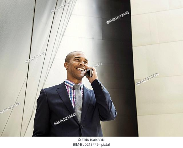 Low angle view of Black businessman talking on cell phone