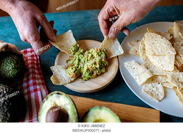 Hands grabbing nachos with guacamole