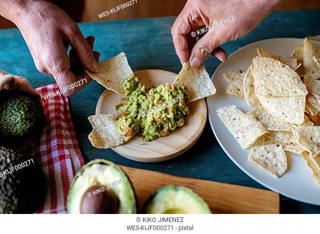 Hands grabbing nachos with guacamole