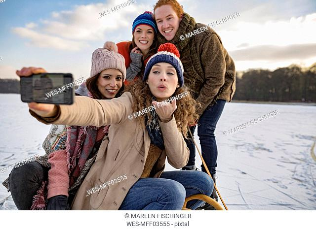 Friends taking a selfie on frozen lake