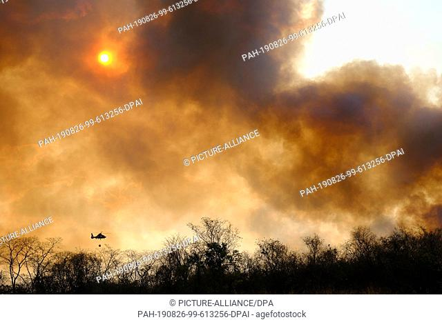 24 August 2019, Bolivia, Santa Cruz: A helicopter flies over Santa Cruz, where there are big forest fires. Numerous forest fires are currently raging in South...