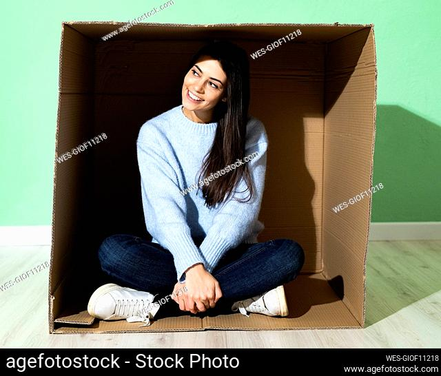Smiling woman looking away while sitting in cardboard box