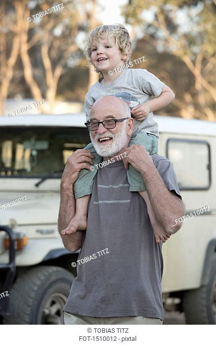Happy grandfather carrying boy on shoulders outdoors