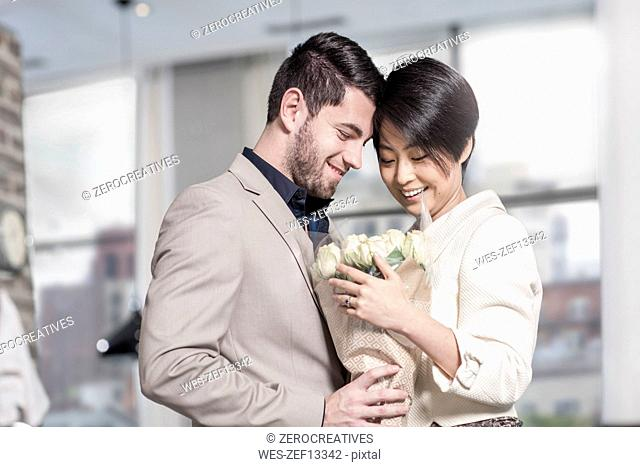 Man handing over roses to woman at home