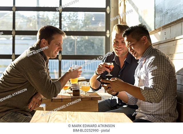 Friends texting on cell phone in brew pub