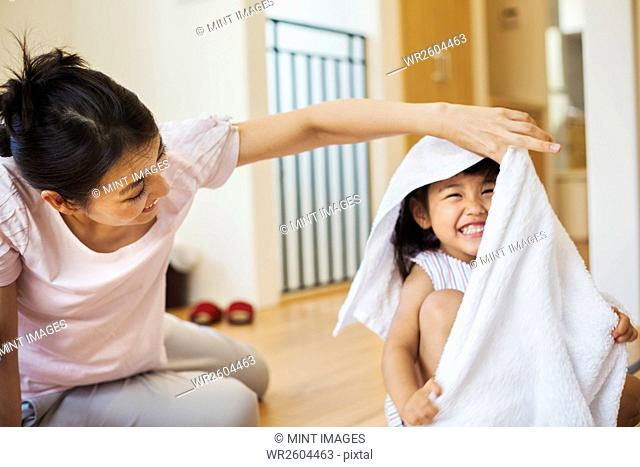 Family home. A woman and her daughter folding clean laundry