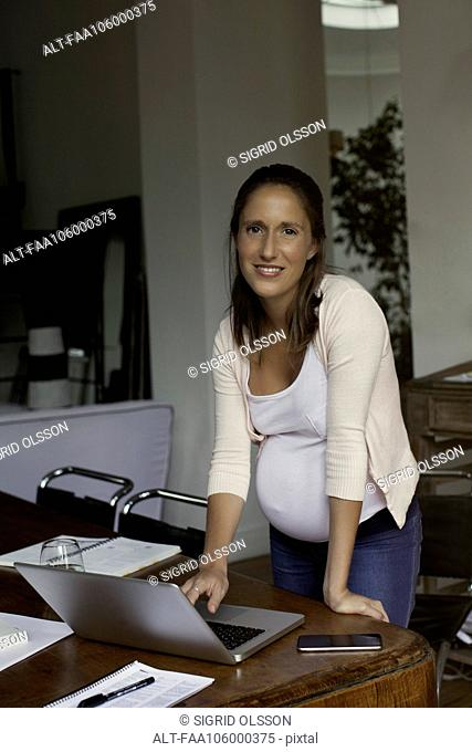 Pregnant woman working from home, portrait