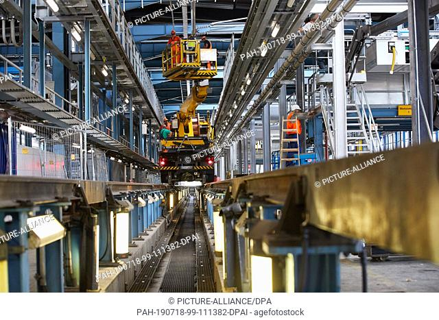 18 July 2019, Hamburg: Workers on a lifting truck lay overhead lines at a maintenance track in the ICE plant in Langenfelde
