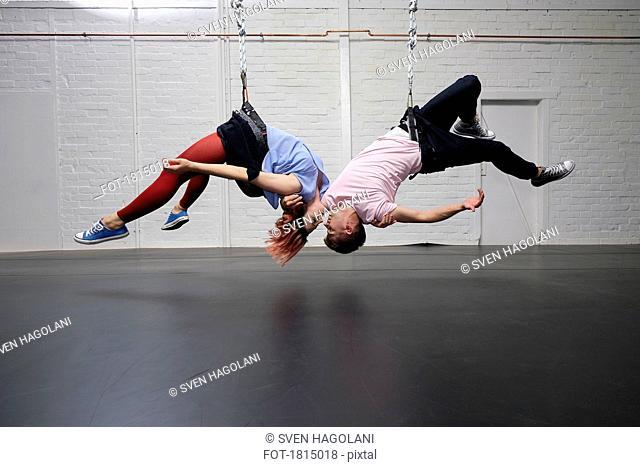 Modern aerialist dancers performing, hanging upside-down