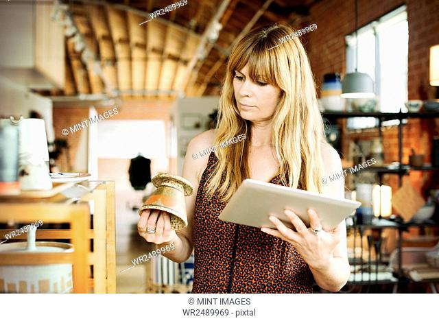Woman in a shop, holding a digital tablet and small ceramic pot