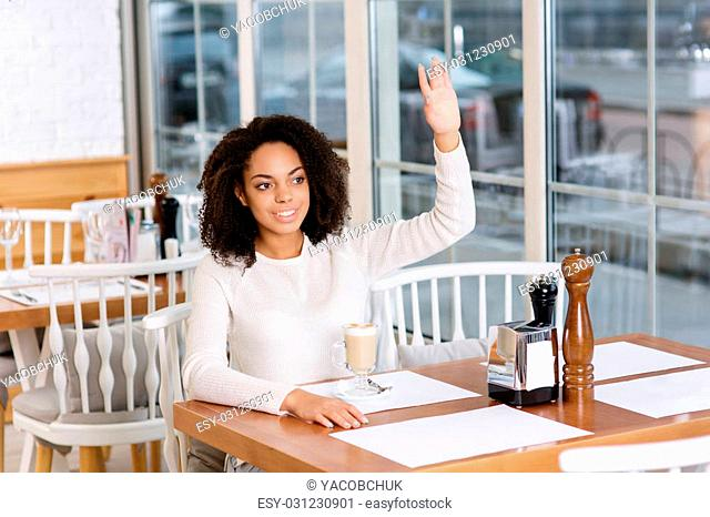 Over here. Young pleasant-looking lady is smiling politely while waving to her waiter