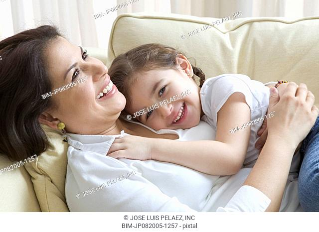 Mother and young daughter laying together on couch