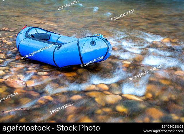 a blue pacraft (one-person light raft used for expedition or adventure racing) on a shallow, rocky t a shallow river